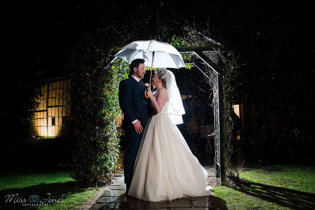 Couple in the rain outside the Barns Hotel bedford on their wedding day