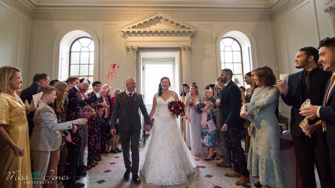 Confetti throwing inside Chicheley Hall on a wedding day