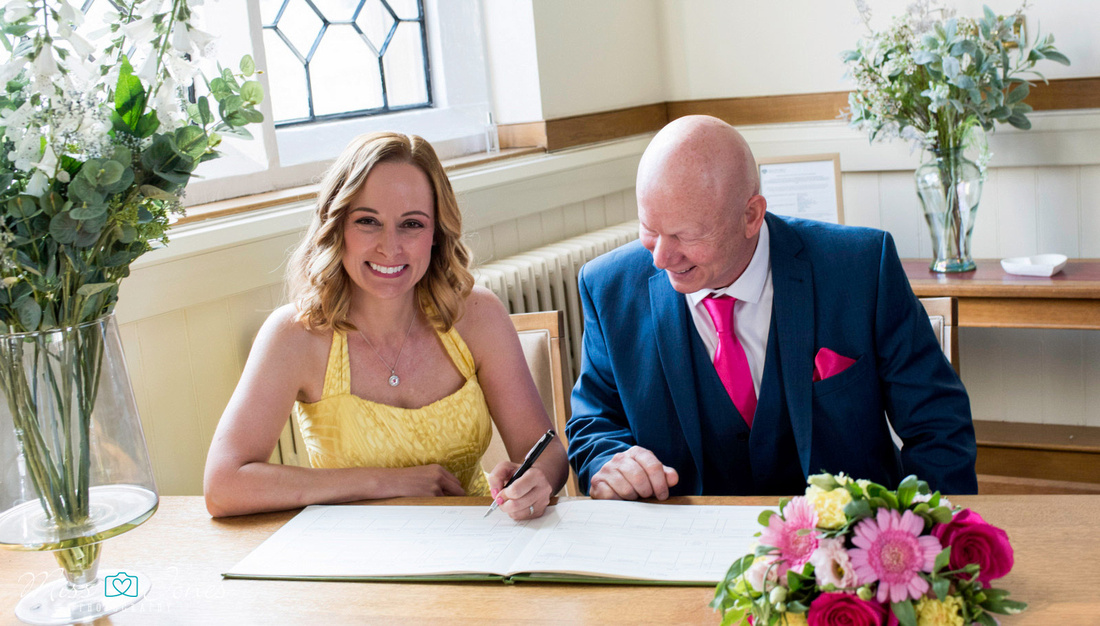 Wedding couple signing the register at the Old Town Hall, Bedford
